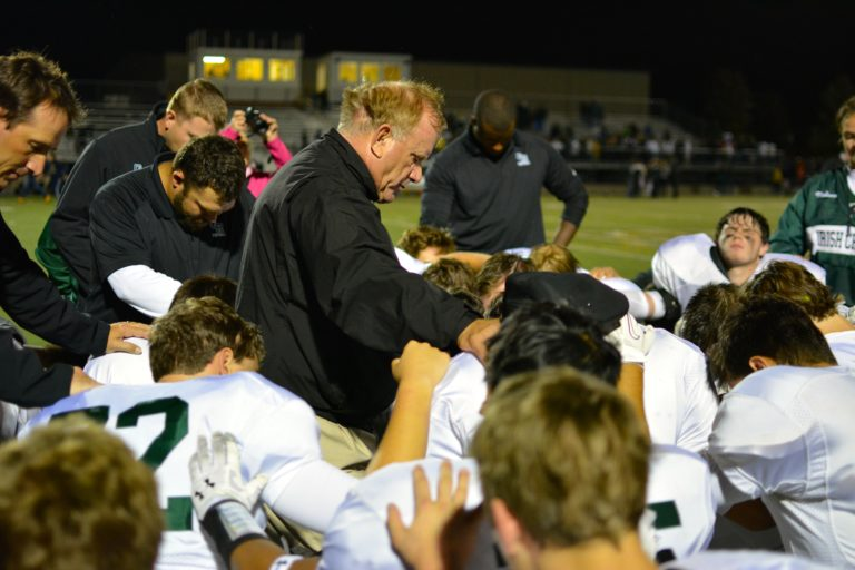 Deacon Dave leads our football players in prayer.