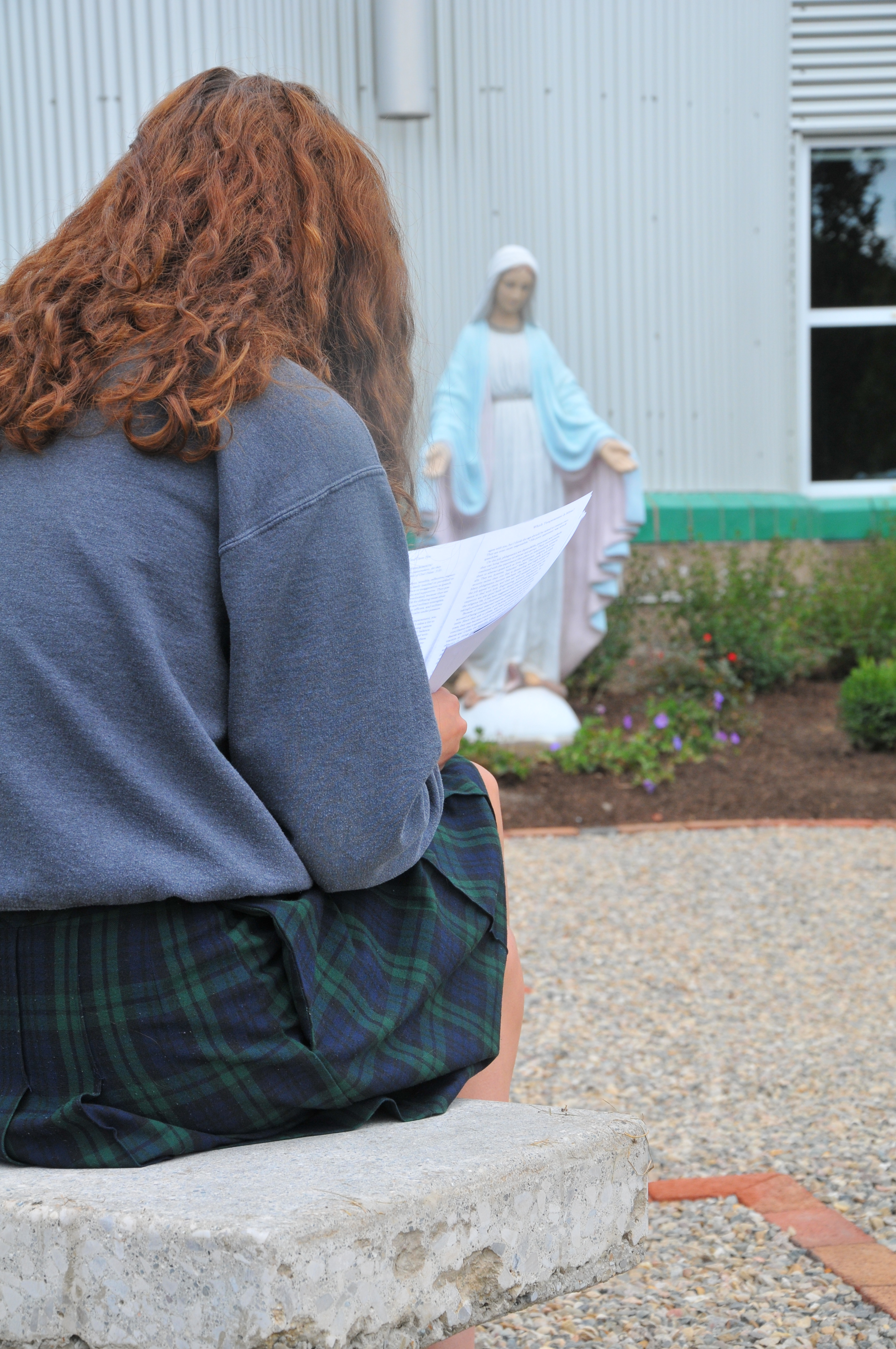A student studies in the Marian Garden.
